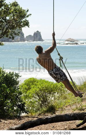 Man on rope swing at beach