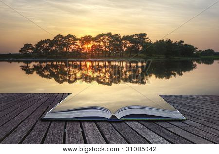 Creative Concept Image Of Refelcted Lake Sunset Coming Out Of Pages In Magical Book