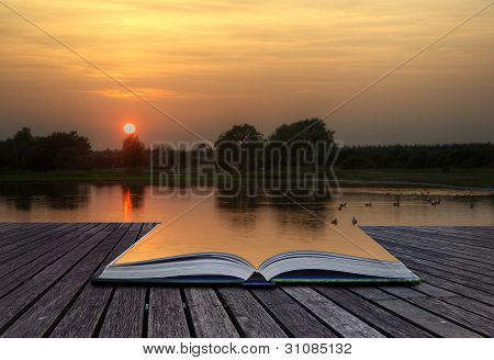 Creatice Concept Image Of Setting Sun Reflected In Still Lake Water Coming Out Of Pages In Magical B