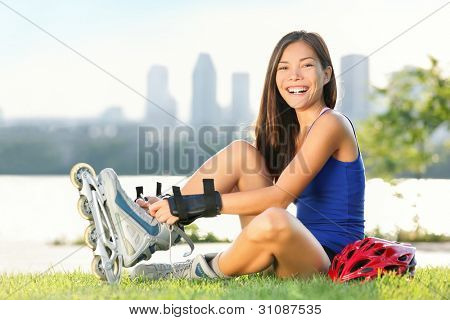 Roller skate girl skating. Young woman putting on skates going rollerblading in urban city park. Beautiful multiracial young woman smiling at camera with Montreal skyline in background.