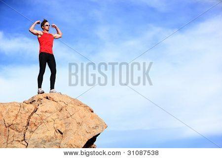 Success - winner man on mountain top celebrating showing muscles in sporty outfit. Fit caucasian male fitness model cheering on top of the world.