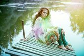 Beautiful hippie girl is sitting on the platform in the background of lake outdoor. Contemporary boh poster