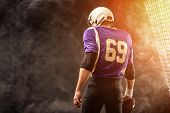 American Football Player Holding Ball In His Hands In Smoke. Black Background, Copy Space. The Conce poster