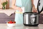 Woman Holding Container With Delicious Fresh Yogurt Made In Modern Multi Cooker At Table, Closeup poster