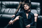 Passionate Handsome Man Sitting Near Sexy Woman In Bdsm Costume On Black Leather Sofa poster