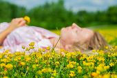 Happy Woman Lying On The Field In Grass With Yellow Flowers Outdoors. Enjoy Nature. Allergy Free. poster