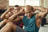 Muscular african american man doing sit ups at gym with other people in background. Mature black man poster