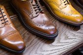 Brown full grain leather shoes on wooden display in men shoes boutique store. poster