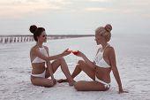 Cheers! Happy Two Girl Friends In Sexy Bikini Having Fun On White Salty Beach At Sunset. Girlfriend  poster