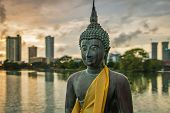Statue Of Buddha Made Of Bronze In A Peacefull Pose, In Front Of A Cityscape On The Beira Lake In Co poster