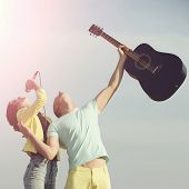 Pretty Girl, Singer, Singing To Mic With Handsome Man, Guitarist, With Guitar, Musical Instrument. Y poster