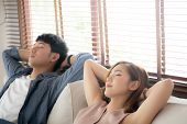 Young Asian Couple Smile Relax Comfortable On Sofa In The Living Room In Holiday, Family Leisure And poster
