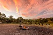 Campfire With Fire Burning In A Campground In The Australian Outback And A Beautiful Sunset Sky Over poster