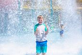 Young boy getting soaking wet while at an outdoor water park. Lots of water splashing water behind t poster