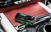 Closeup Inside Vehicle Of Wireless Green Leather Key Ignition On Natural Wood Panel. Wireless Start  poster