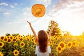 Happy Young Woman Walking In Blooming Sunflower Field Throwing Hat Up And Having Fun. Summer Vacatio poster