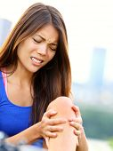 Sports injury. Woman with pain in knee joint sport workout. Young woman fitness model outside.