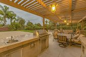 Outdoor Kitchen And Dining Area Under A Pergola At The Spacious Patio Of A Home poster