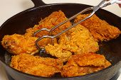 stock photo of fried chicken  - Chicken cooking in a cast - JPG