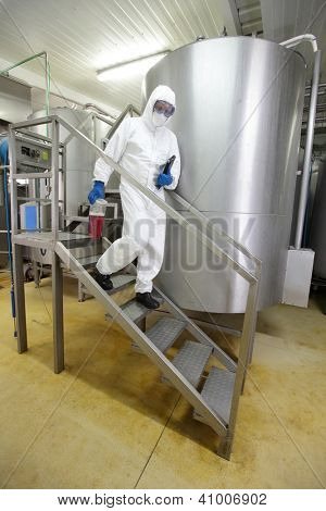 engineer with tablet and  sample in plastic container walking down the stairs  in industrial interior
