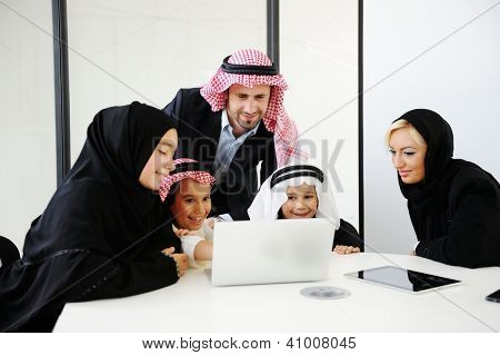 Middle eastern people with children at office working on laptop