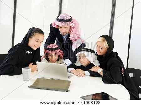 Arabic Muslim business people with children at office working on laptop