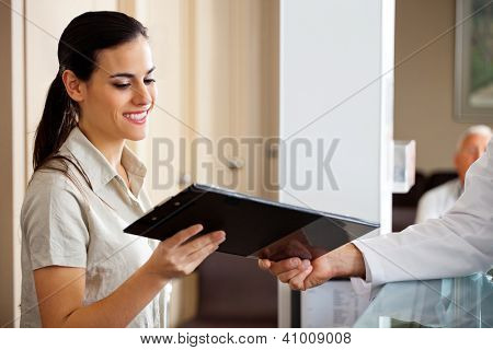 Happy young receptionist taking clipboard from doctor while standing at reception