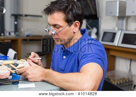 Dental Lab Technician Appying Porcelain To Mold