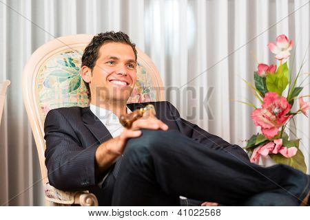Young man sitting on the chair in the hotel room and is happy