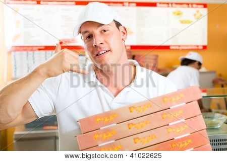 Man holding several pizza boxes in hand and asking you to order pizza for delivery