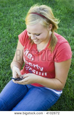 Girl Smiling At Text Message Sitting On Grass