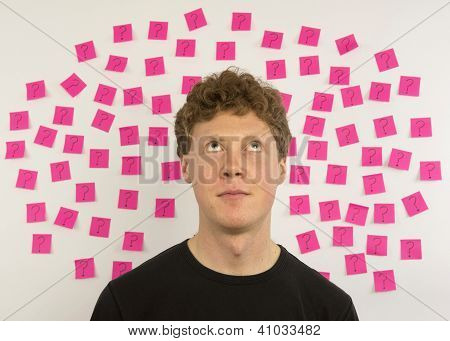 Young man with pink sticky notes and question marks thinking about decision making