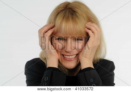 Closeup of stressed out female office worker with hands to head and pained expression