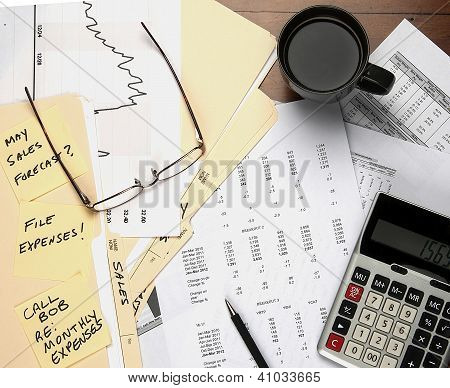 View of desk with financial papers calculator coffee cup and glasses