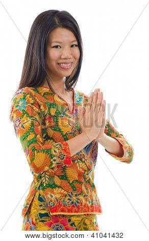 Southeast Asian girl in a traditional greeting gesture, isolated white background