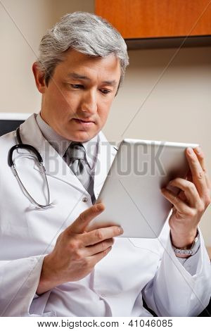 Serious mature male doctor in lab coat looking at digital tablet
