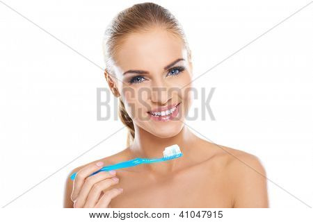 Beautiful smiling woman with bare shoulders holding a toothbrush and toothpaste, fresh studio portrait on white