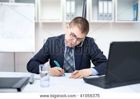 Portrait Of Young Business Man In The Office Doing Some Paperwork And Talking On Cell Phone