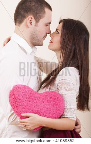 Couple in love on valentines day hugging while girl holds heart