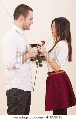 Couple in love on valentines day drinks wine while girl holding rose