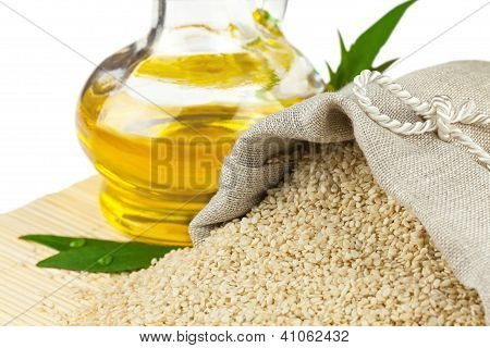 Sack Of Sesame Seeds And Glass Bottle Of Oil On Mat