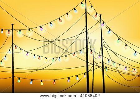 Hanging glowing light bulbs at sunset
