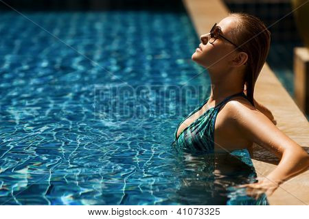 Portrait of young attractive woman having good time in swimming pool