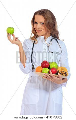 Portrait of a smiling woman doctor holding fresh fruits. Isolated over white background.