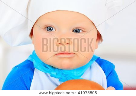 Cute small baby in the cook costume is eating his bagel.