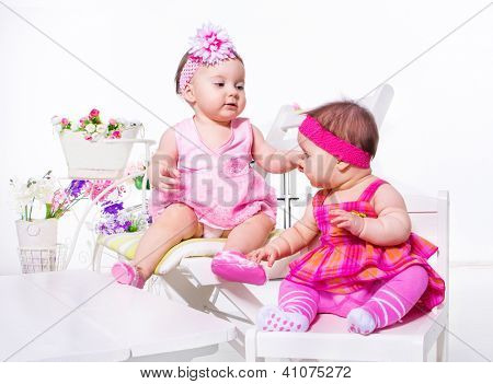 Baby girls in beautiful dresses sit on white chairs