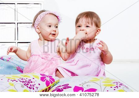 Babies in pink dresses playing on the floor
