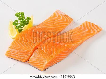 two salmon fillets with lemon and parsley