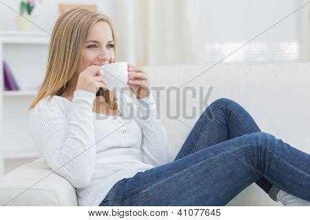Junge Frau Kaffee zu trinken, wie sie weg auf Couch zu Hause aussieht