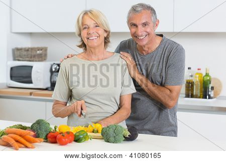Happy couple cutting vegetables together in the kitchen